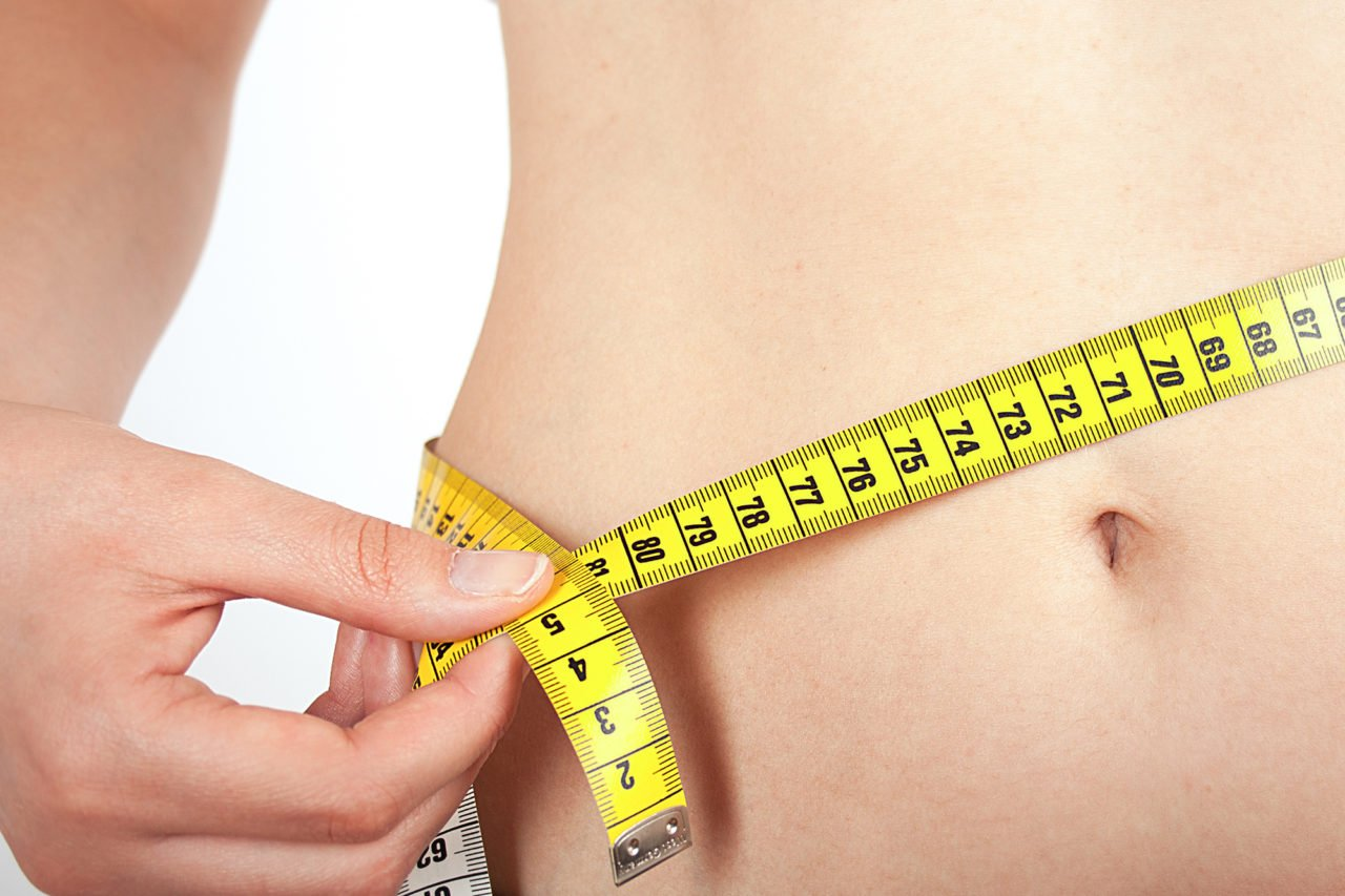 Belly of a young woman with tape measure