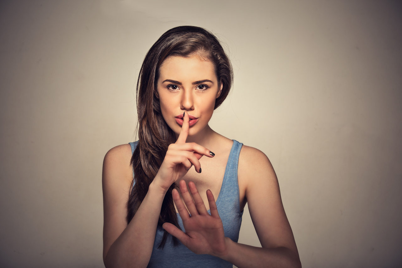Portrait of young beautiful woman with finger on lips isolated on gray wall background