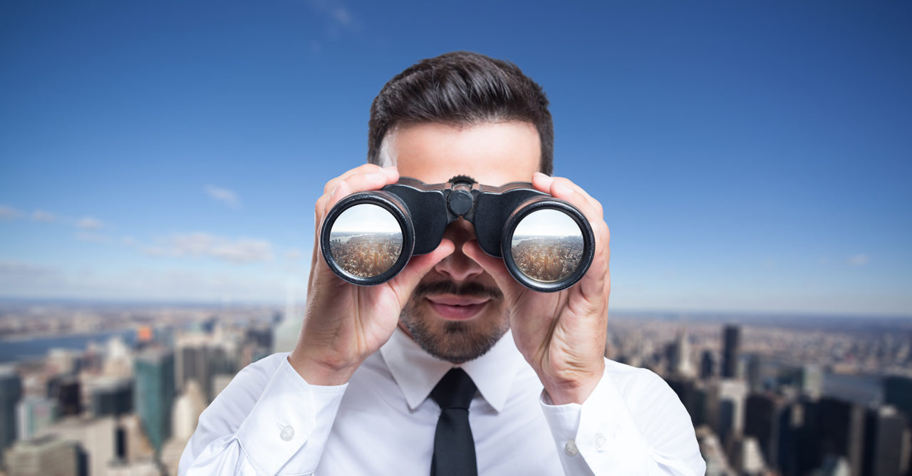 Businessman using binoculars to look at the city