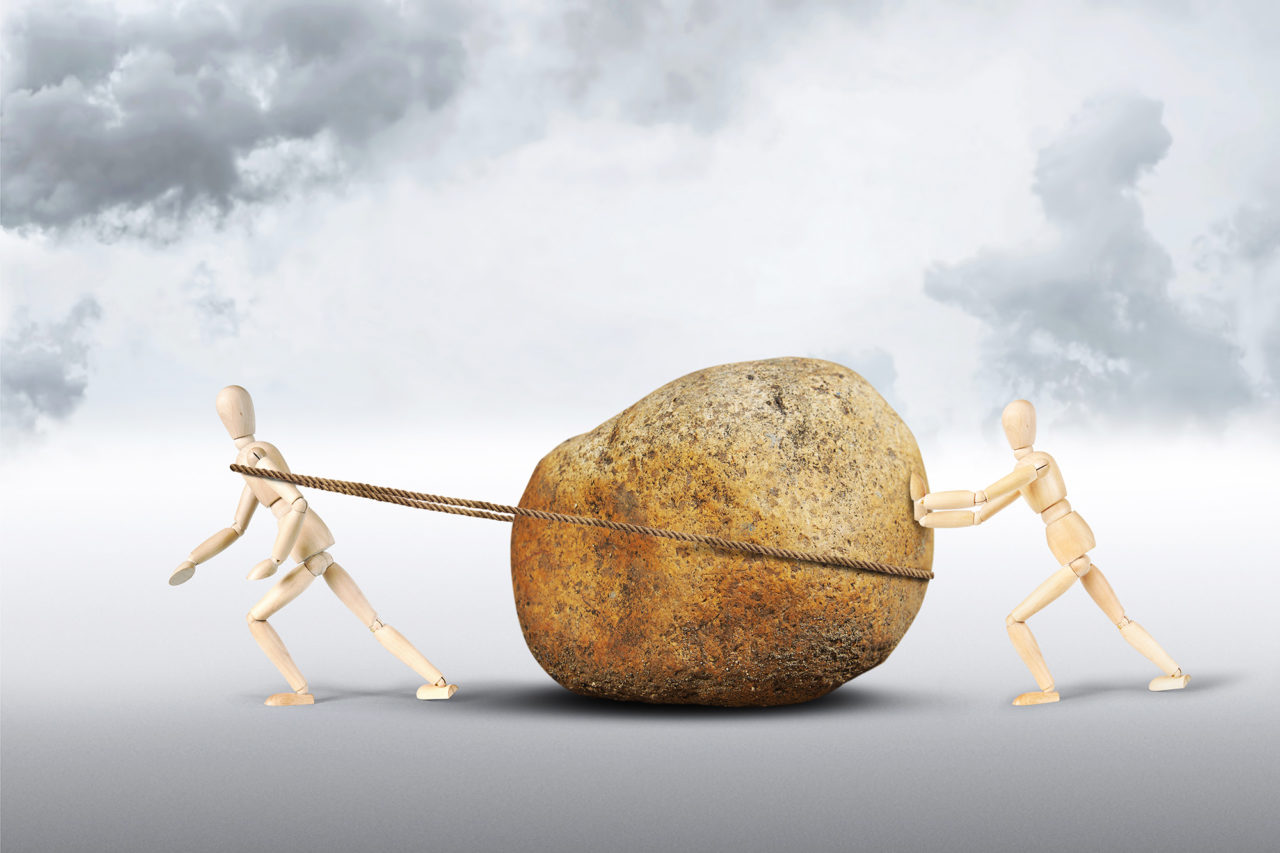 Two men move a huge stone. Abstract image with wooden puppets