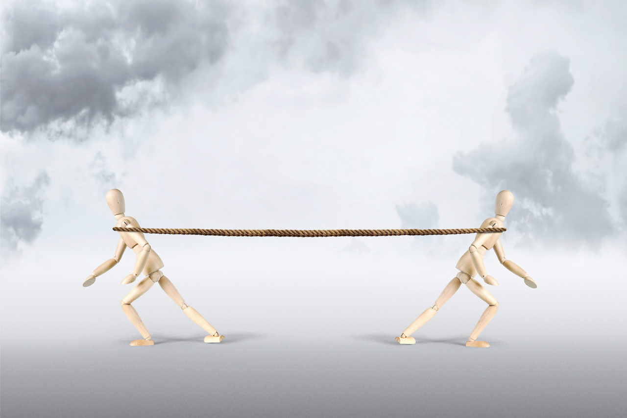 Two men pull a rope in opposite directions. Tug of war. Abstract image with wooden puppets