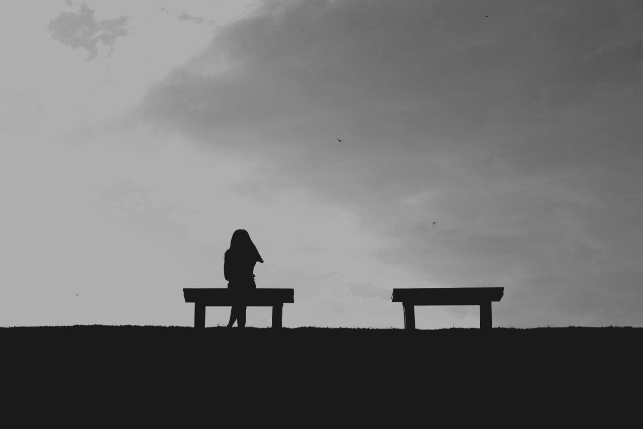 The silhouette of woman sitting alone with grey sky, concept of lonely, sad, alone, person space