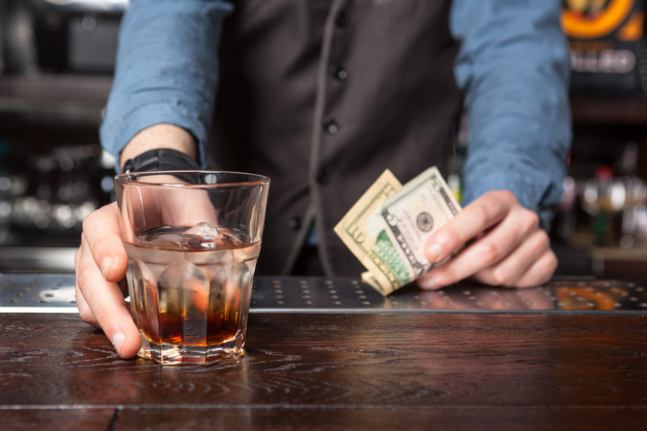 Barman with whiskey glass and money in his hands.