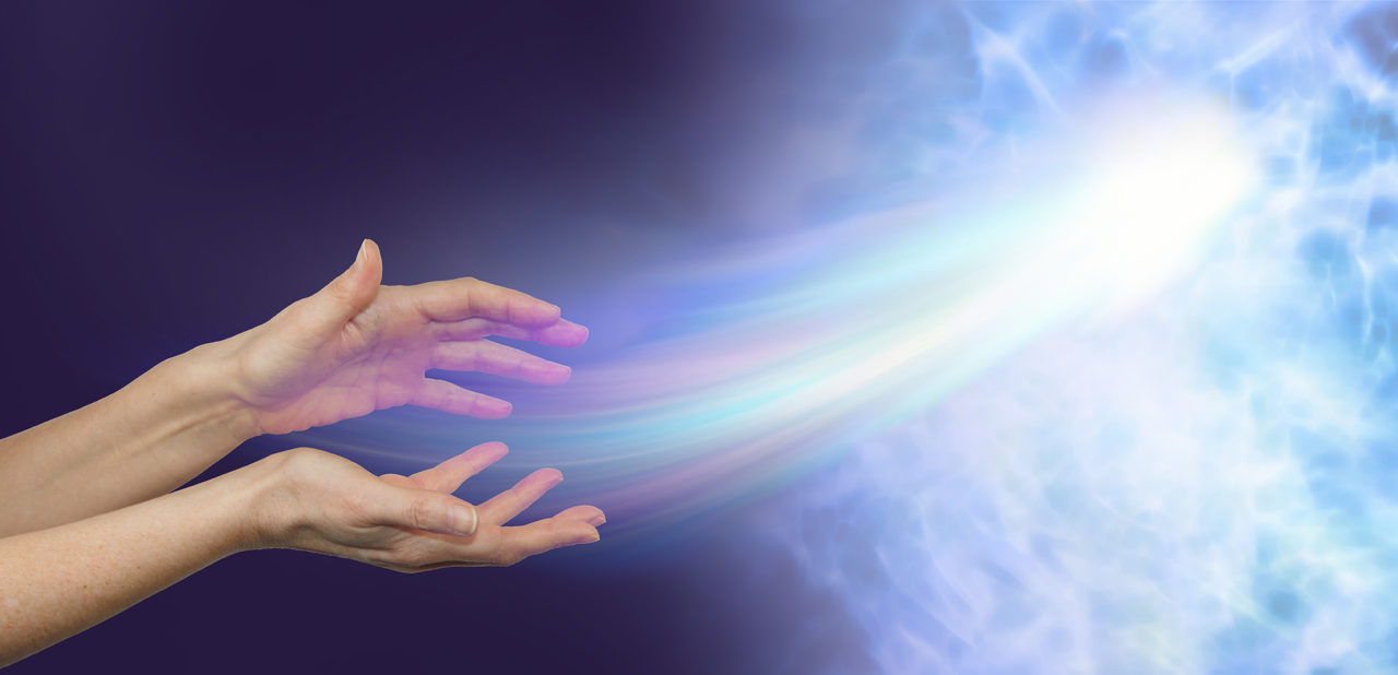 Peace at last - female hands on a darkness to light background and a soul energy formation moving out towards the light depicting soul release
