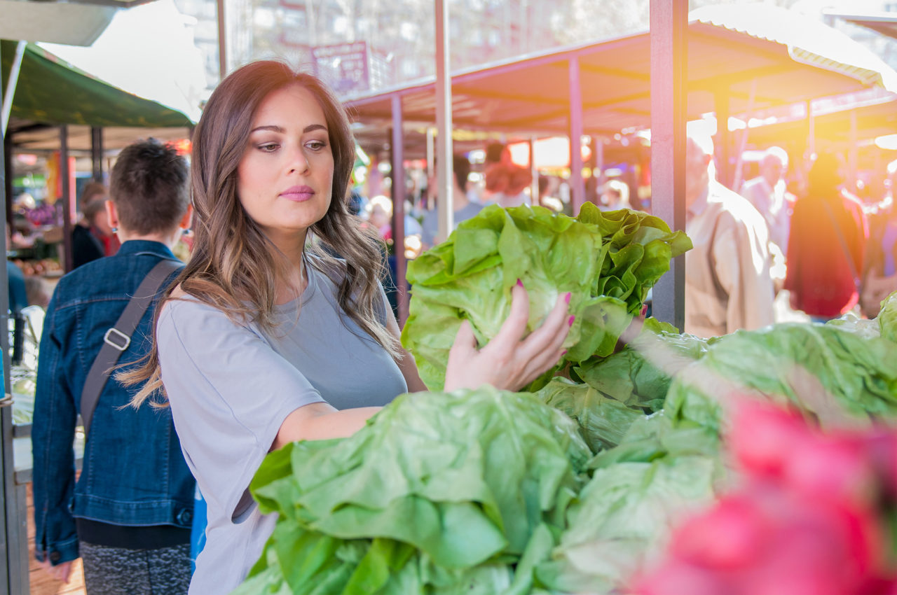 Woman buying fruits and vegetables at local food market. Market stall with variety of organic vegetable. Portrait of beautiful young woman choosing green leafy vegetables