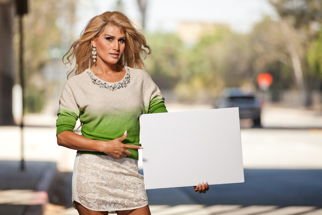 Latina Transgender female pointing at blank poster board sign