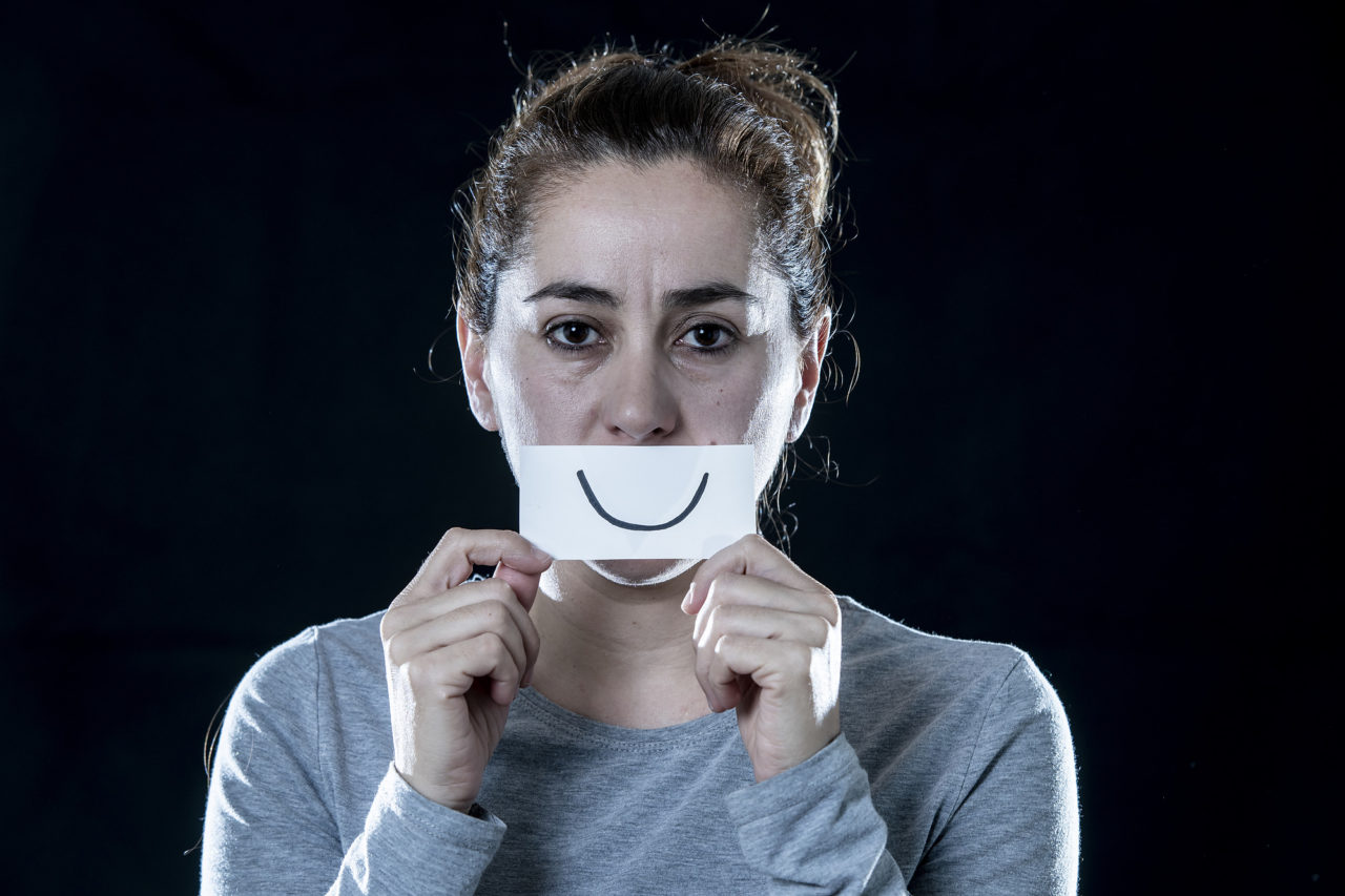 depressed latin woman covering her sad face with a paper cut out