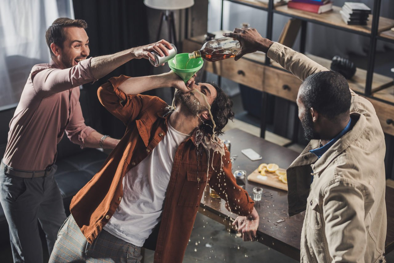 high angle view of man drinking from funnel while friends pourin