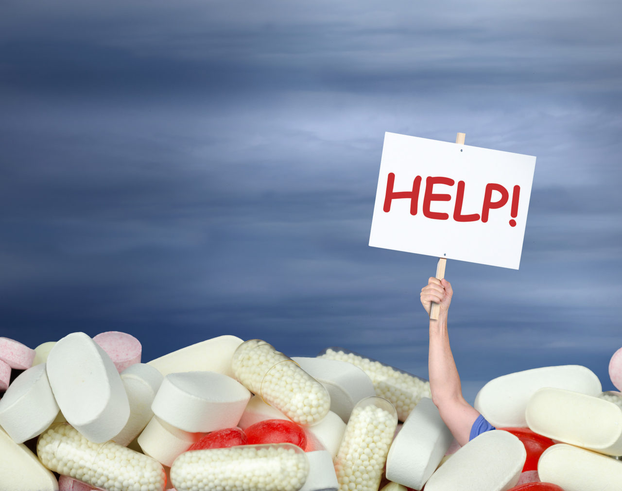A huge pile of various pills with a man's hand coming out of the pills holding a sign that says HELP!