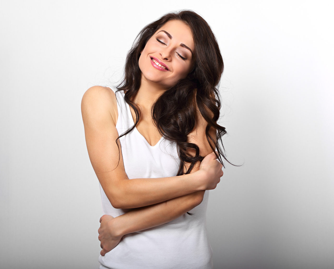 Happy sporty woman hugging herself with natural emotional enjoying face on white background
