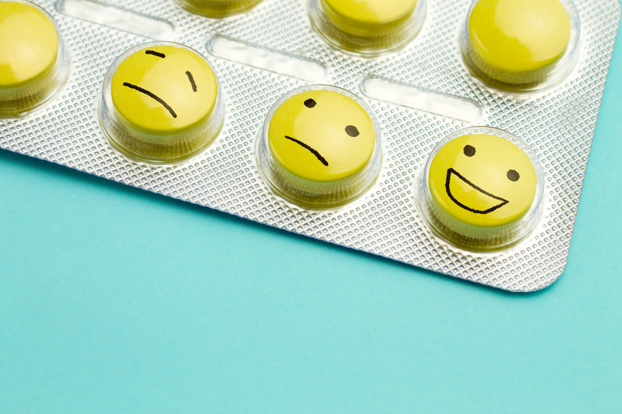 Yellow pills and funny faces in a blister on a blue background