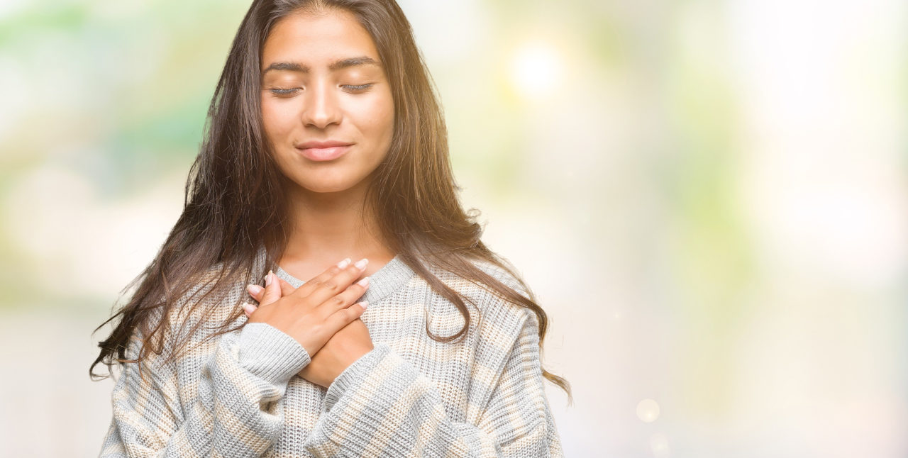 Young beautiful arab woman wearing winter sweater over isolated background smiling with hands on chest with closed eyes and grateful gesture on face.