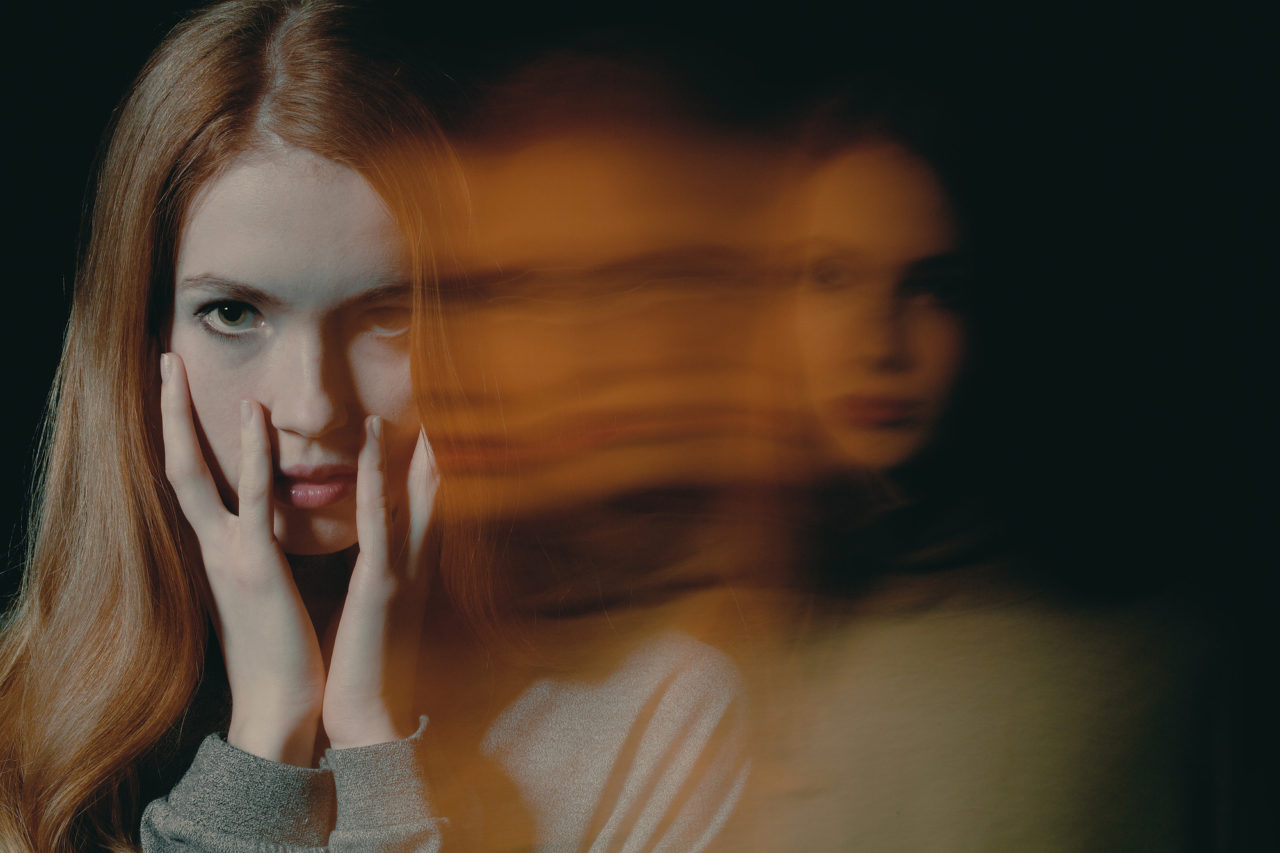 Pretty young redhead girl with anxiety disorder hiding her face