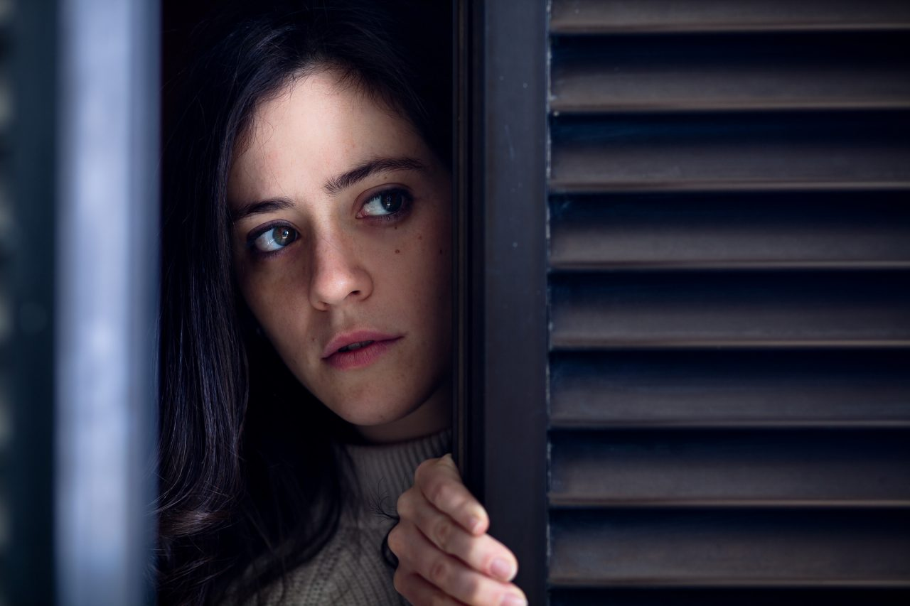 Worried Woman Watching Outside from a Wooden Window Shutter