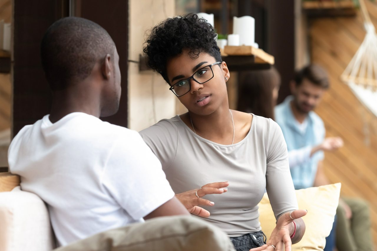 Focused African American woman talking with man in cafe