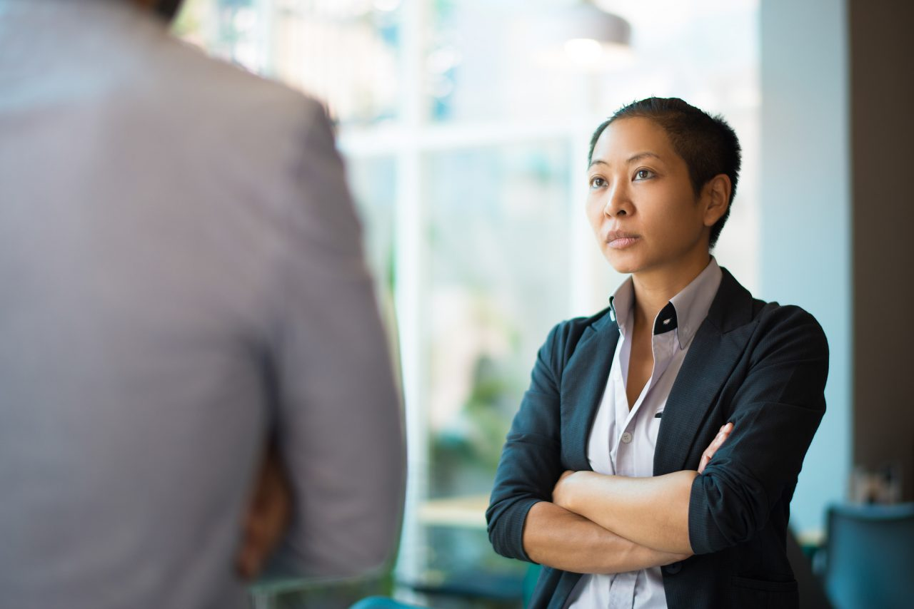 Tense Asian businesswoman looking at male partner with crossed arms.