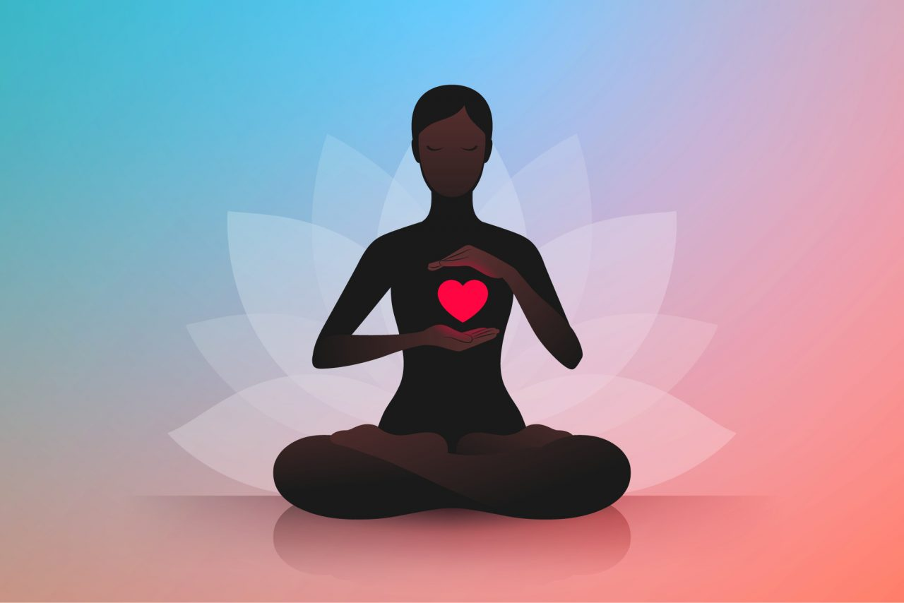 Woman sitting in lotus position and holding hands near her red heart