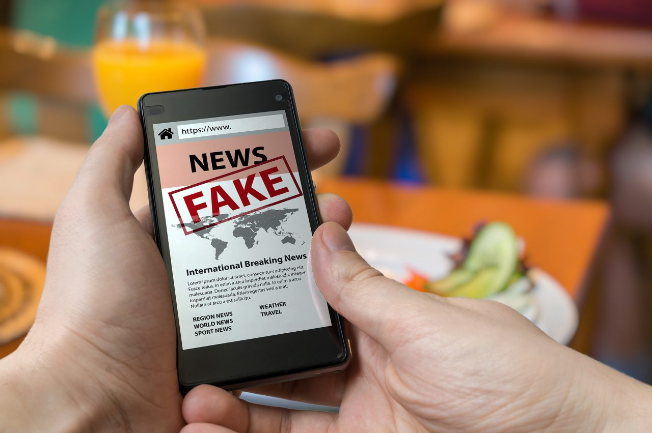 Man is holding smartphone and reading fake news on internet
