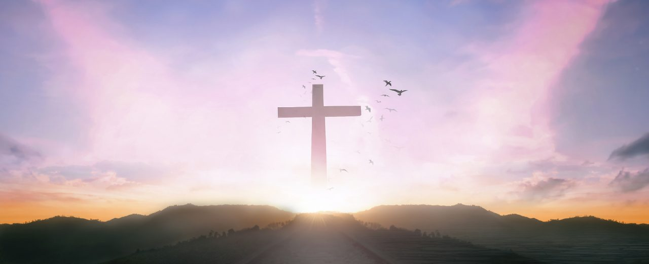 Silhouette cross and birds flying on sunrise background
