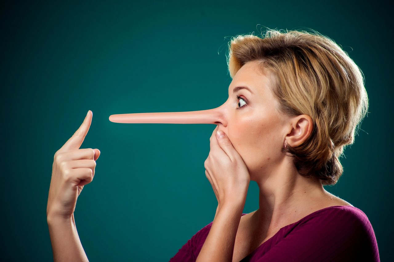 Woman touching her long nose because of lie