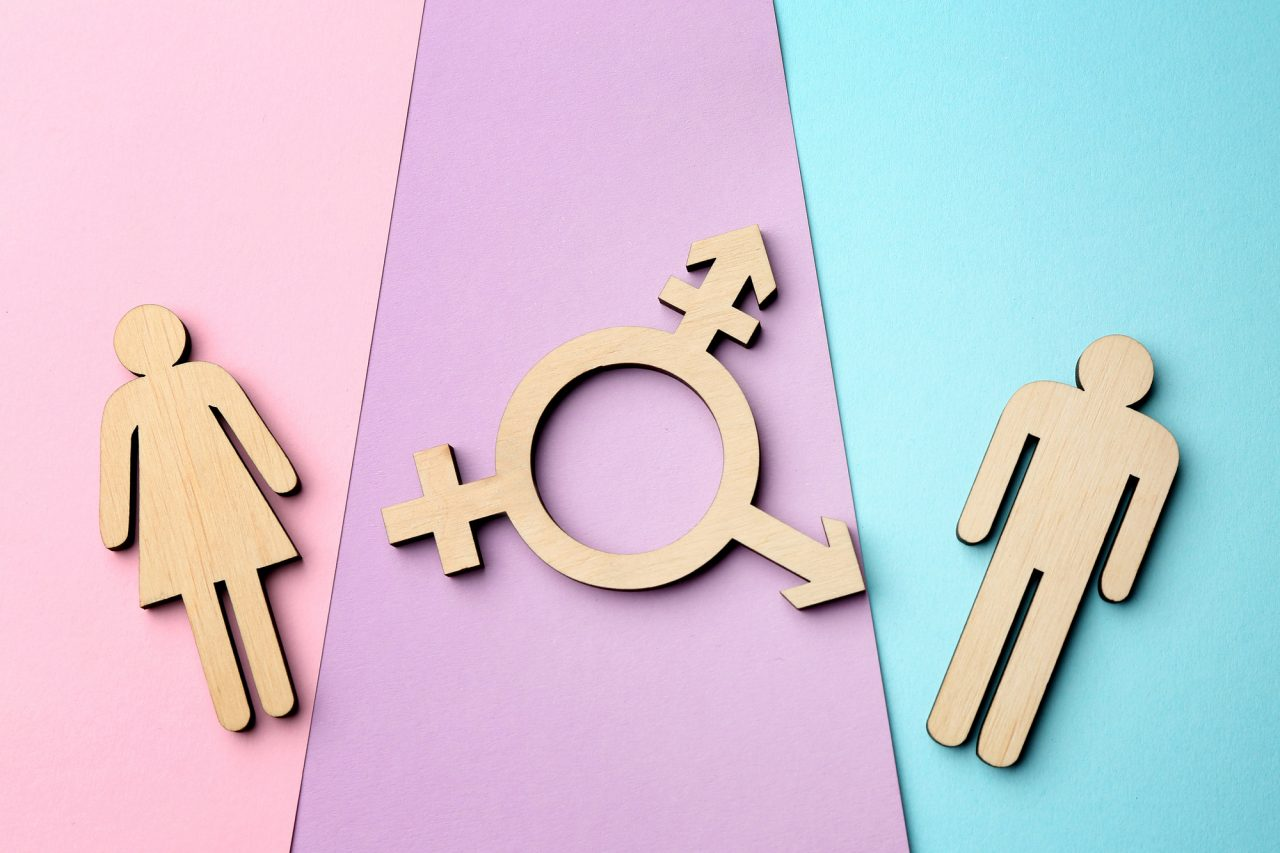 Female and male figures with symbol of transgender