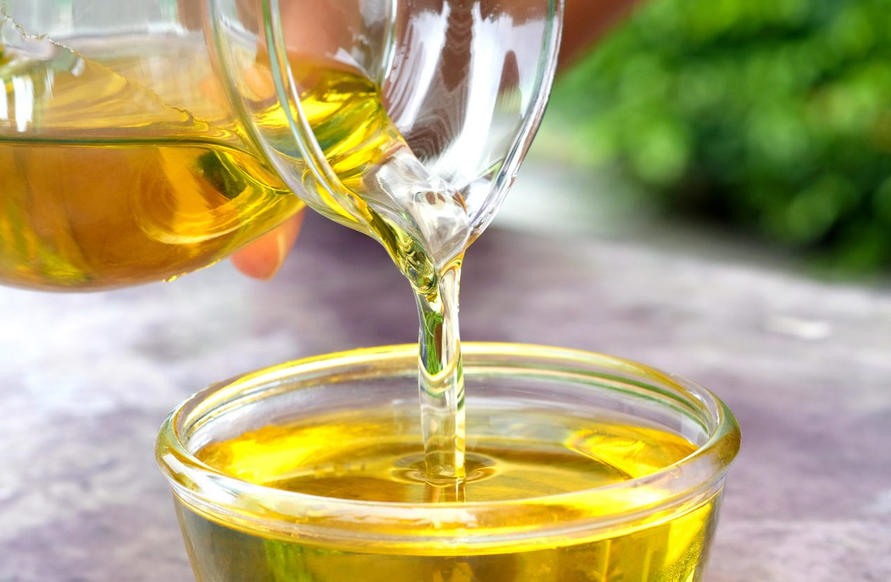 Pouring olive oil in the a glass bowl
