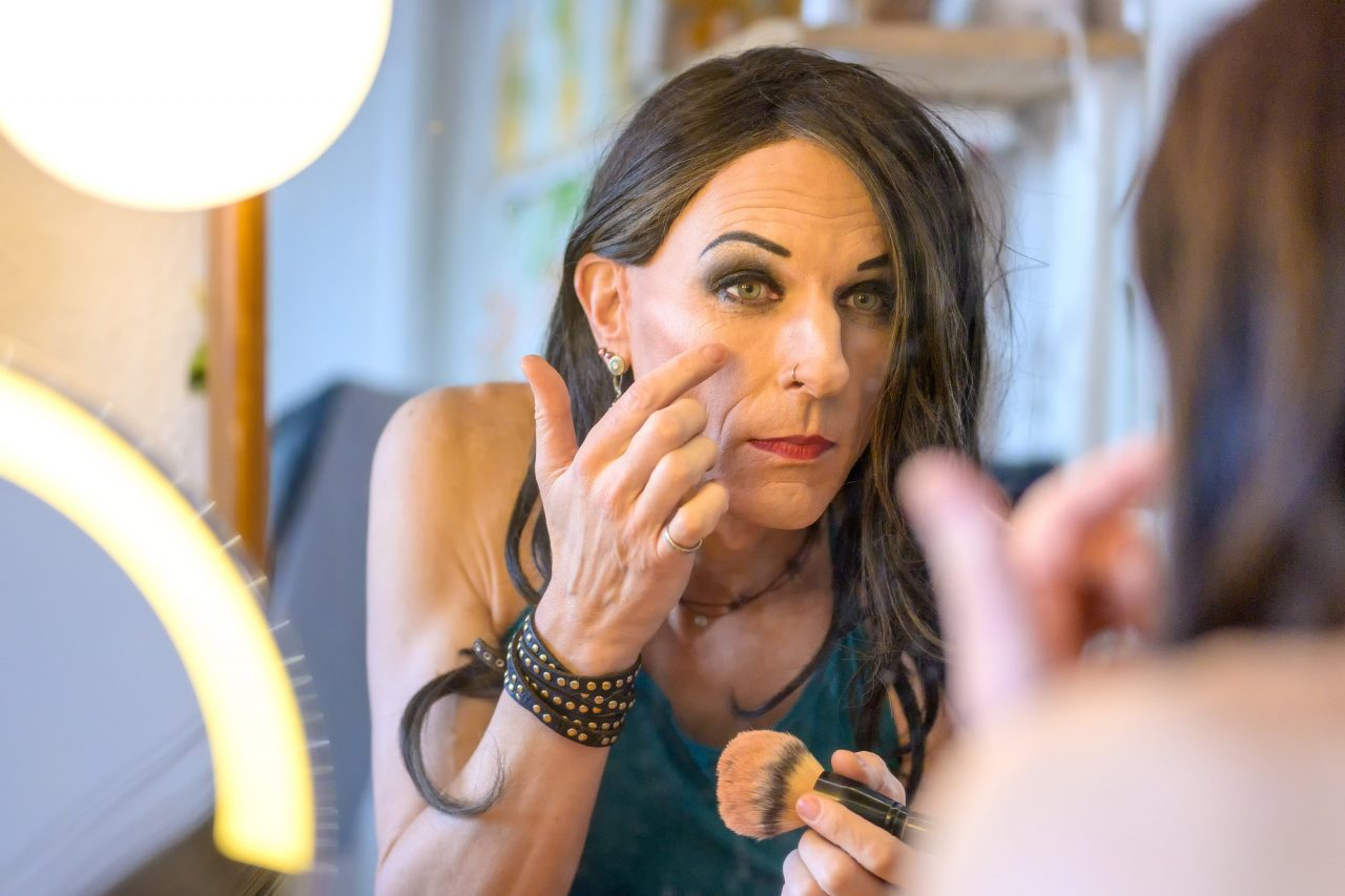 Portrait of transgender woman applying make up