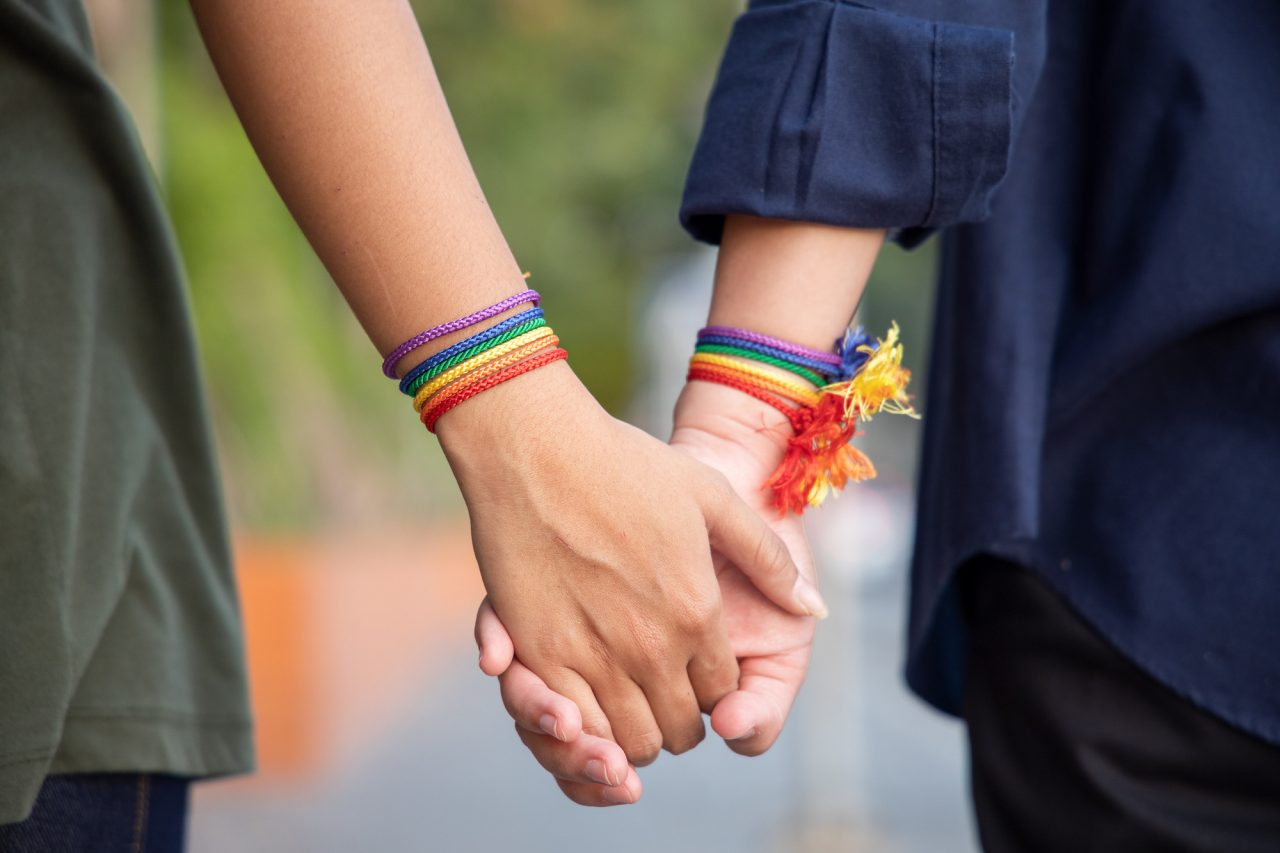 hand of LGBT women holding together with rainbow ribbon symbol